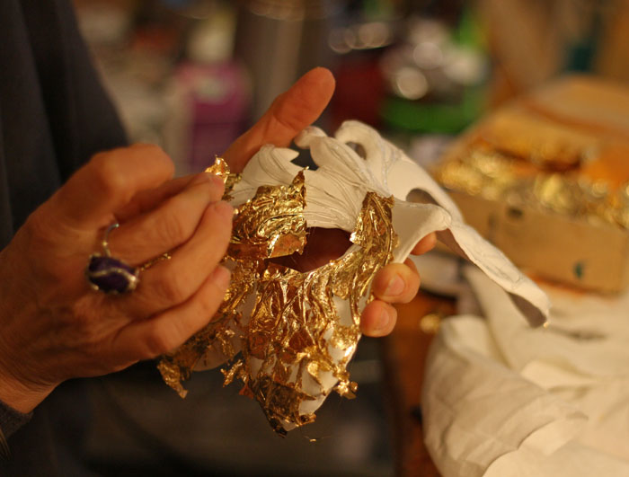 Eliana Giordano, decorating the mask in papier–mâché with metal foil