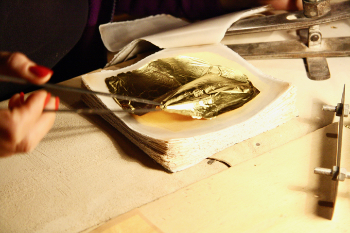 Taking the gold leaf out to trim it in a precise form
